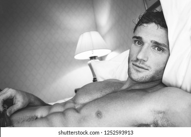 Black and white portrait of good looking man with pecs and abs looking at camera