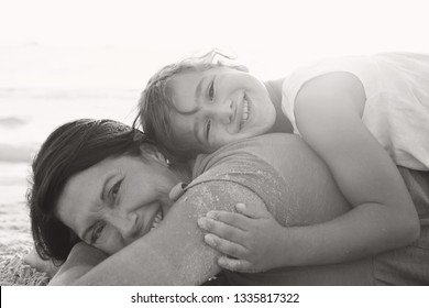 Black and white portrait of grandmother and grand daughter laying on sand with heads together, beach holiday hugging outdoors. Senior and child fun bonding family travel activities lifestyle.