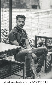 Black and White portrait of a handsome and good looking young male model with fancy hair sitting at a table of a restaurant wearing a knee cut fashionable denim pant