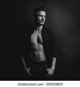 Black and white portrait of handsome guy in naked body with shirt that looking to the left on dark background