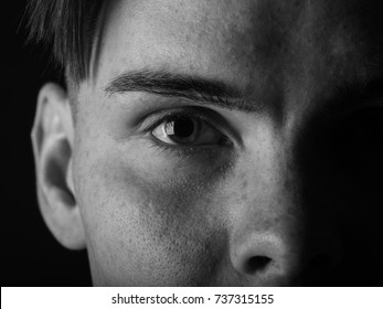 Black and white portrait of a handsome guy. Tired, sad young man on a black background. Stress concept.