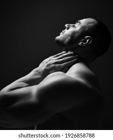 Black and white portrait handsome sexy muscular man, athlete with perfect built body standing soide to camera holding hand at neck, head thrown back and eyes closed over dark background