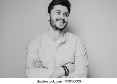 black and white portrait of handsome smiling man isolated on gray studio background posing to the camera