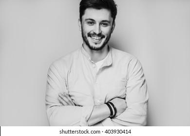 Schwarz-Weiß-Porträt eines gut aussehenden Mannes einzeln auf grauem Studiohintergrund, der die Kamera darstellt