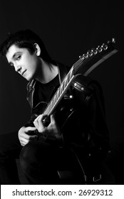 black and white portrait of a handsome young man sitting on the chair and playing guitar