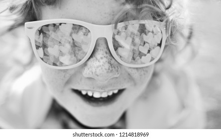 black and white portrait of a happy child, smiling caucasian boy with freckles and curly hair in sunglasses, mirror reflection in glasses is  bokeh with hearts