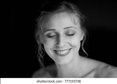 Black and white portrait of a happy and joyful young beautiful woman with closed eyes and gentle smile on her face against a black background
