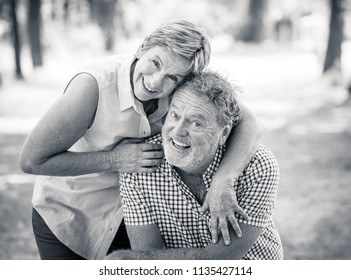 Black and white portrait of a happy smiling senior couple in love, relaxing, dancing and having fun in the park. Being together strong, retirement happy life concept.