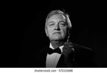 Black and white portrait image of a smart mature man wearing a jacket and bow tie