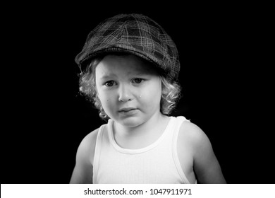 A black and white portrait of a little boy wearing a white tank top crying from one eye. The child has a single tear running down his cheek. The sad child cries from his eyes. There is room for text.