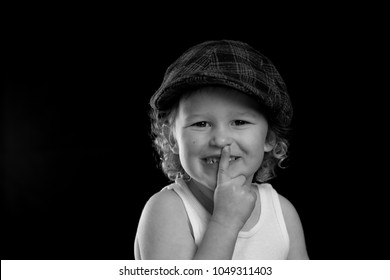 A black and white portrait of a little boy wearing a white tank top who has a secret. The child's fingers are to his lips to say quiet.  There is room for text and words on a solid black background.