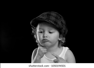 A black and white portrait of a little boy wearing a white tank top thinking and daydreaming.  He may have an idea or is wondering. There is room for text or words with a solid black background.