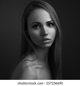 Black and white portrait of a lonely young girl beautiful blonde model on a dark background in the studio