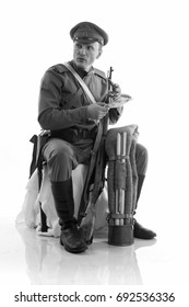 Black and white portrait  Male actor in the form of ordinary soldiers of the Russian army during the First World War dismantles and assembles a rifle against a white background