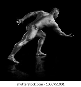 Black and white portrait of male athlete bodybuilder posing on a black background