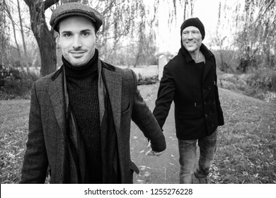 Black and white portrait of male gay couple holding hands and smiling as they walk on park pathway