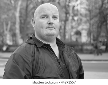 black and white portrait of a male man in black jacket. big man with shaved bald head. close up face head shot.