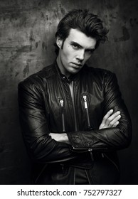 Black and white portrait of a man in a black leather jacket near wall