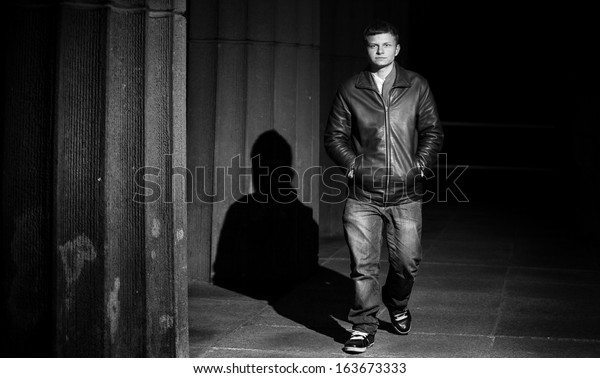 Black and white portrait of man in leather coat walking at night near columns