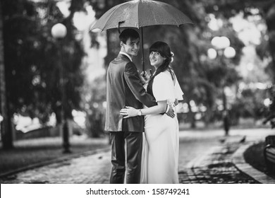 Black and white portrait of married couple standing in park under umbrella