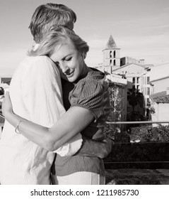 Black and white portrait of mature tourist couple hugging on holiday break, city overview romantic vacation together. Senior man and woman travel, sightseeing, loving leisure recreation lifestyle.