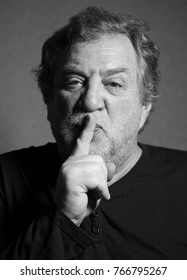 black and white portrait of middle aged caucasian man who put his index finger to his lips, calling for silence