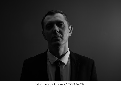Black and white portrait of an office worker, concept of dismissal, lost a job. Businessman went bankrupt looking upset at the camera in the studio