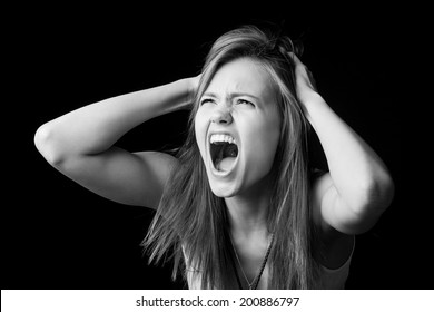 Black and white portrait of a openmouthed girl who scream and cries and holds his head.