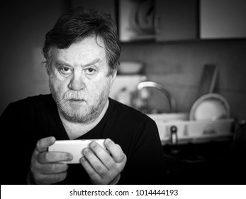 Black and white portrait of pensive mature man with cell phone