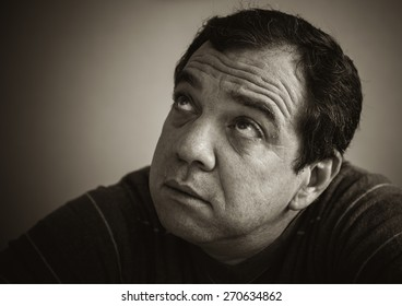Black and white portrait of a pensive mature man. Lookup.