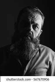 Black and white portrait picture of a senior man with a full beard. Close up head shot with close up of face. Grumpy serious facial expression.