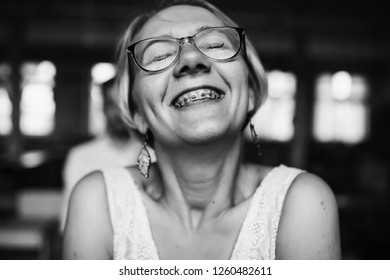 Black and white portrait of pretty blonde woman in glasses smiling with her braces
