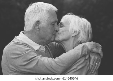 Black and white portrait of romantic seniors kissing while standing in each other's arms outdoors with dark background