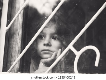 Black and white portrait of Sad little girl looks through window with lattice