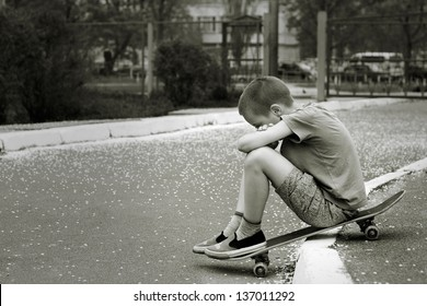 Black and white portrait of sad lonely child who sitting on skateboard in  park