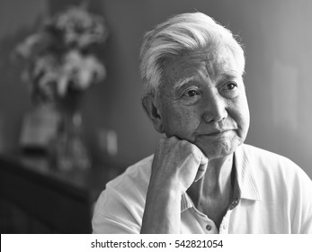 black and white portrait of a sad lonely asian senior hand on chin looking away thinking.