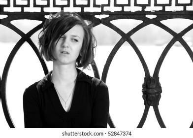 Black and white portrait of sad young female sitting near embankment balustrade