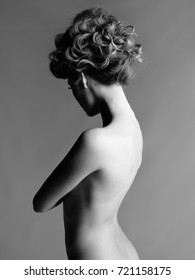 Black and white portrait of sensual nude woman with elegant hairstyle on gray background