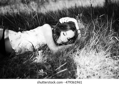 Black and white portrait of sexy brunette girl in flower top slipping on long grass. Female lying in sunny countryside.