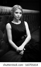 Black and white portrait of sexy woman in black dress sitting on leather couch at restaurant