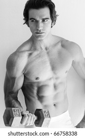 Black and white portrait of a shirtless fitness model working out with weights