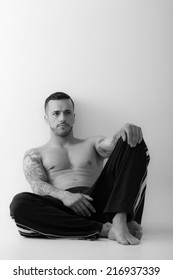 Black and white portrait of Shirtless muscular attractive young man model wearing sweatpants sitting over white background