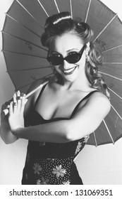 Black And White Portrait Of A Smiling Vintage Lady With Classical Hair, Makeup And Fashion Dancing With A Retro Umbrella