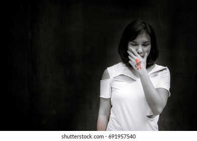 "Black and white portrait, Stop violence against women, international women's day, concept of stop abusing woman, woman holding her hand with the word ""STOP"" written on it, hard contrasts"
