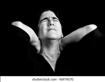 Black and white portrait of a stressed woman suffering from neck pain on a black background with space for text