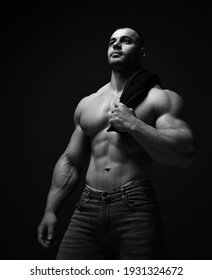 Black and white portrait of strong muscular man, athlete, sportsman stands with naked chest holding shirt on his shoulder and looks up at copy space at copy space on dark background