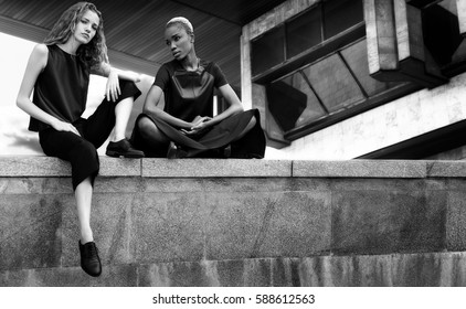 Black and white portrait of two girls of girlfriends, curly blonde and slender dark-skinned girl with short white hair. Summer walk to the sights of the city