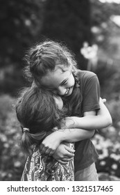 Black and white portrait of Two Happy little girls laughing and hugging at the  summer park.