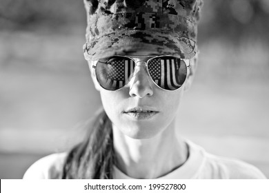 Black and white portrait of us army woman with american flag reflection in the sunglasses