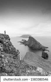A black and white portrait view of an adventurer admiring a moody skyline and mountainous landscape in the Faroe Islands, notably with Drangarnir sea stack and Tindholmer in the distance.